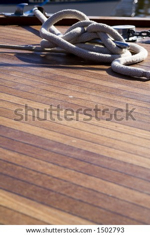 Wooden boat deck with rope. - stock photo