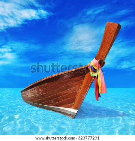 wooden boat in the blue sea - stock photo
