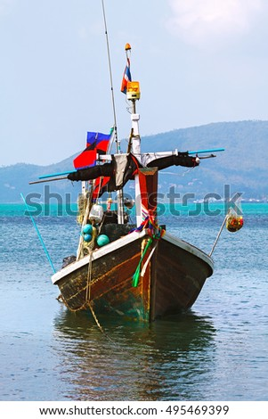 wooden boat in the turquoise sea water with fishing gear. Thailand