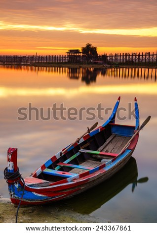 Wooden boat in Ubein Bridge at sunrise, Mandalay, Myanmar (World longest wooden bridge) - stock photo