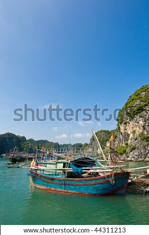 Wooden boat near one of the many fish farms located at Ha Long Bay.
