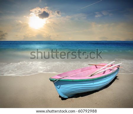 Wooden boat on a beach at sunset - stock photo