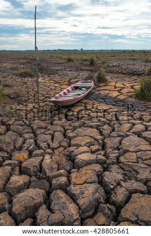 Wooden boat on drought land with blue sunset - stock photo