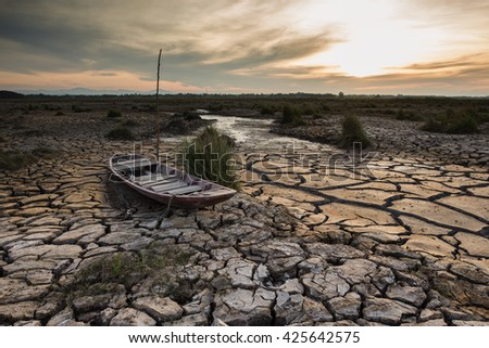 Wooden boat on drought land with sunset - stock photo