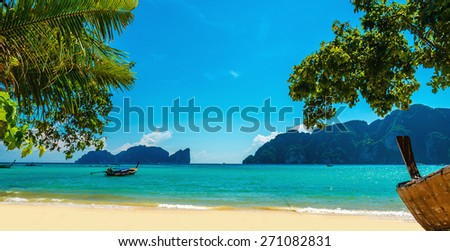Wooden boat on the sandy shore of the exotic beach on a background of blue sky and azure sea, Phi Phi Islands, Thailand - stock photo