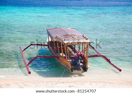 Wooden boat on the white sand beach. Gili islands, Indonesia. - stock photo