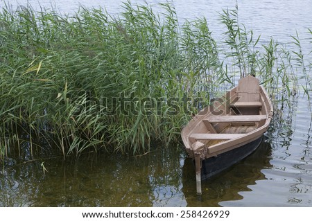 wooden boat over the side of lake - stock photo