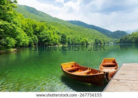 Wooden boats at pier on mountain lake - stock photo