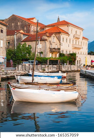 Wooden boats float moored in Perast. Kotor Bay, Montenegro - stock photo