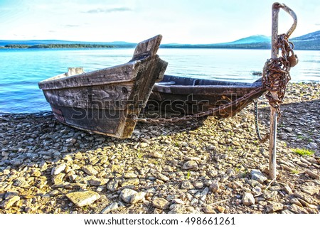 wooden boats on bank of lake in summer