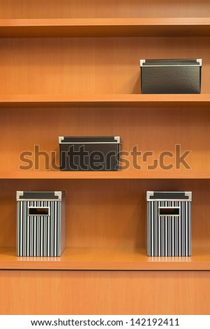 wooden bookshelf with boxes - stock photo