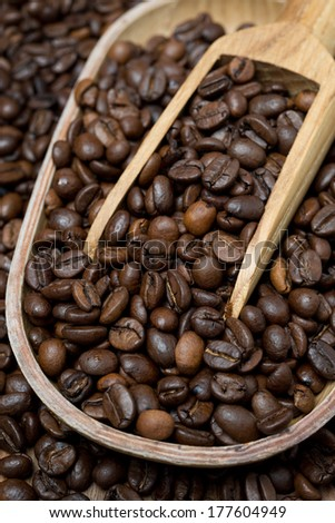 wooden bowl and scoop with coffee beans, vertical, close-up