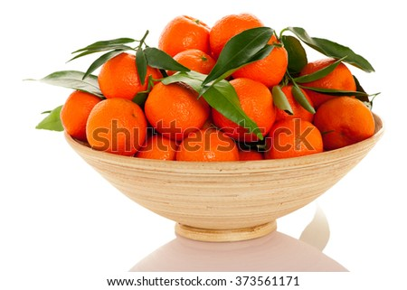 Wooden bowl filled with fresh orange mandarin citrus fruit with green leafs, isolated over white background. - stock photo
