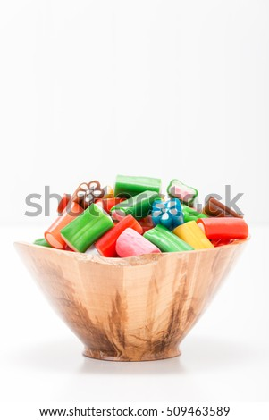Wooden bowl filled with soft chewy colorful candies.