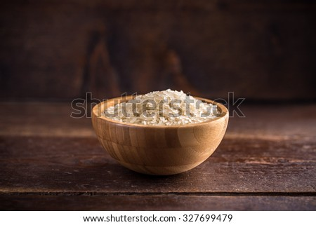 Wooden bowl full of basmati rice - stock photo