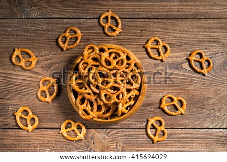 Wooden bowl full of mini pretzels with salt on wooden background, top view - stock photo