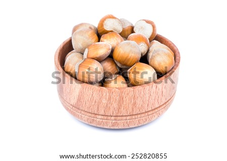 Wooden bowl full of raw hazelnuts in shell - stock photo