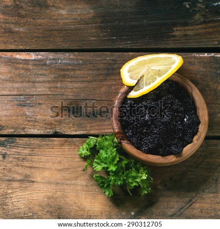 Wooden bowl of black caviar with lemon slice and parsley over old wooden table. Top view. Square image - stock photo