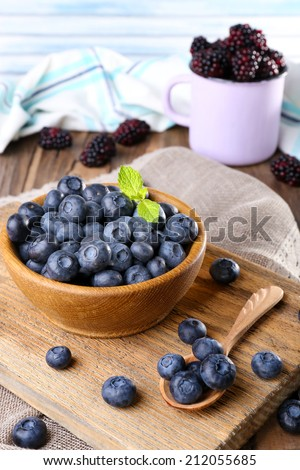 Wooden bowl of blueberries and metal mug of blackberries on cutting board on sacking napkin on wooden table on light background
