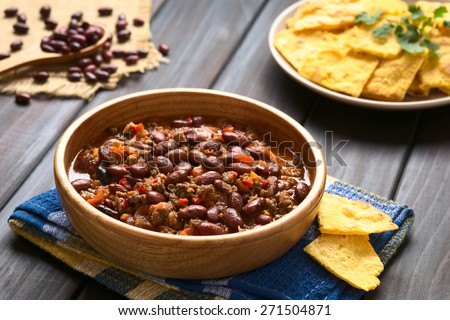 Wooden bowl of chili con carne with homemade tortilla chips in the back, photographed with natural light (Selective Focus, Focus in the middle of the chili) - stock photo