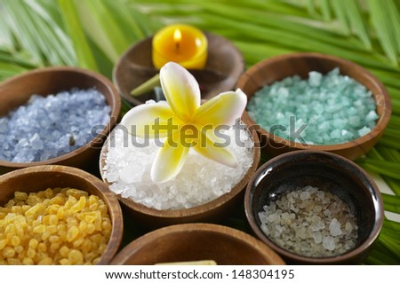 wooden bowl of color sea salt with ,candle , frangipani on leaf