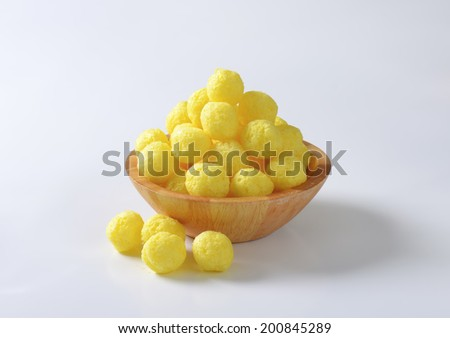 wooden bowl of corn puffs  - stock photo