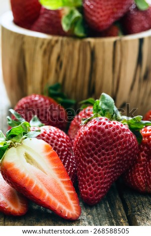 wooden bowl of fresh strawberries on old wooden table
