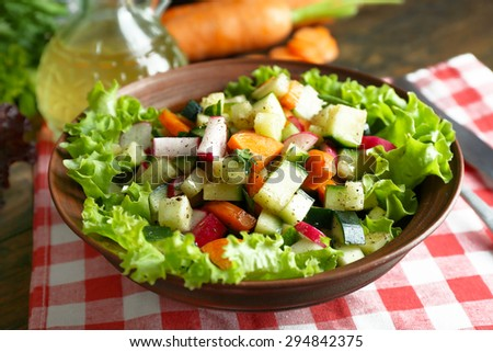 Wooden bowl of fresh vegetable salad on napkin, closeup