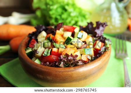 Wooden bowl of fresh vegetable salad on napkin, closeup - stock photo