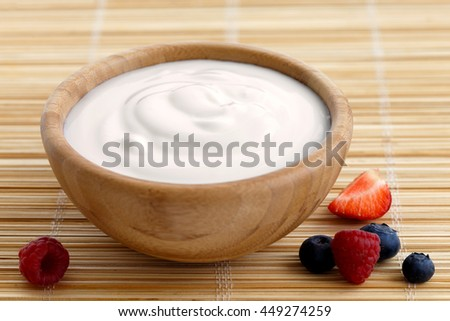 Wooden bowl of fruit yogurt on bamboo matt next to berries.