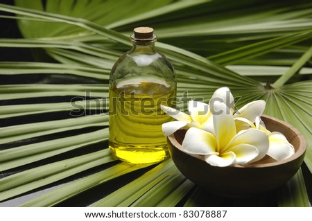 Wooden bowl of plumeria on and spoon on palm leaf texture - stock photo