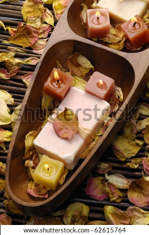 Wooden bowl of soap with rose withered petals - stock photo