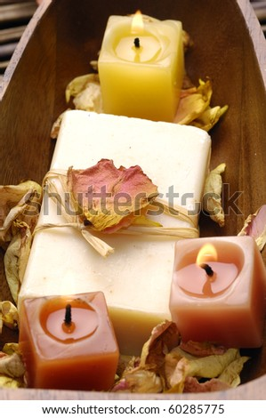 Wooden bowl of soap with rose withered petals on bamboo mat - stock photo
