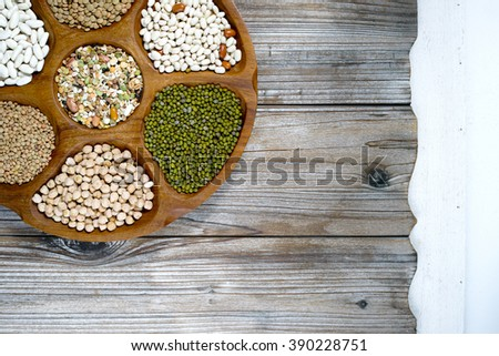 Wooden bowl of various legumes (chickpeas, lentils, green lentils, green mung,beans) on wooden background - stock photo