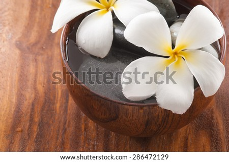 Wooden bowl of white frangipani and stones on board - stock photo