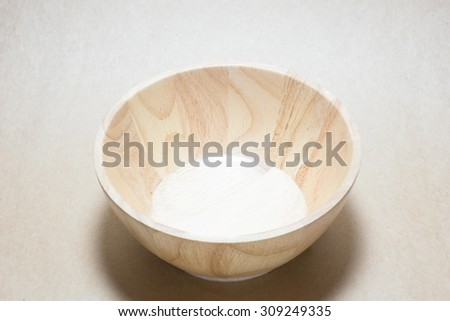 Wooden bowl on brown paper
