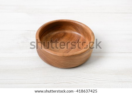 Wooden bowl. on white wooden surface. Wooden Tableware. Environmentally friendly goods. Durable material. Naturally beautiful goods. Strength material. Safe to use. - stock photo