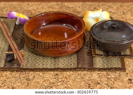 Wooden bowl with a cup of soup With chopsticks on a wooden table