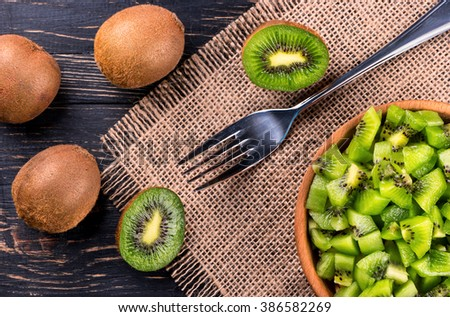 Wooden bowl with a salad of kiwi fruit and a fork on the table top view - stock photo