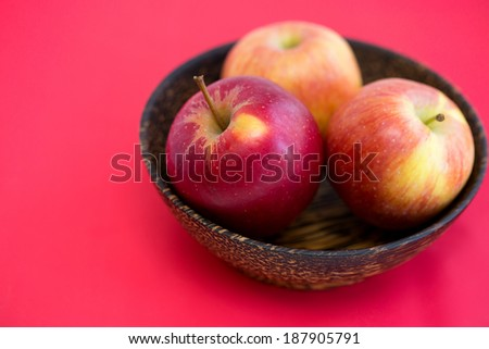 wooden bowl with apples on a red background - stock photo