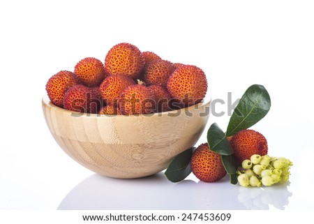 Wooden bowl with arbutus unedo fruits isolated on a white background - stock photo