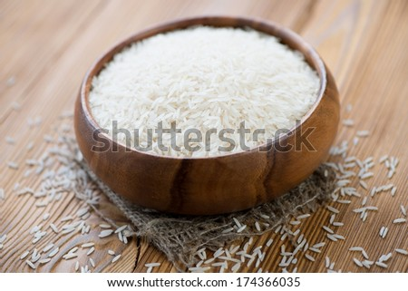 Wooden bowl with basmati kernels, horizontal shot