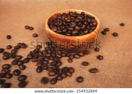wooden bowl with coffee beans lying on brown parchment - stock photo