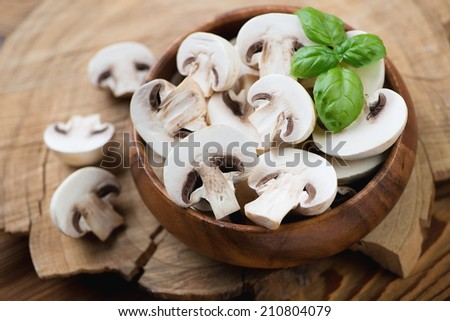 Wooden bowl with fresh champignons and green basil, close-up - stock photo