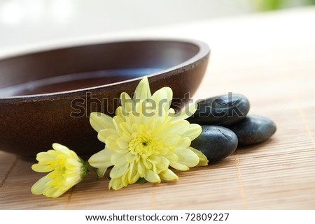 Wooden bowl with hot stones and chrysanthemum for spa - stock photo