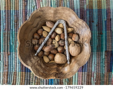 wooden bowl with mixed nuts and nutcracker on colorful woven tablecloth - stock photo
