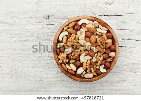 Wooden bowl with mixed nuts on white table from above. Healthy food and snack. Walnut, pistachios, almonds, hazelnuts and cashews. - stock photo