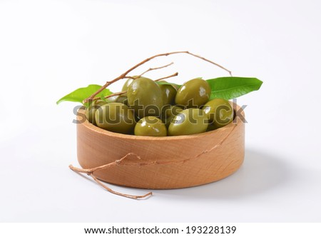wooden bowl with pickled green olives, decorated with twigs and leaves - stock photo