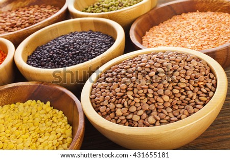 Wooden bowls of various lentils on a wooden background - stock photo