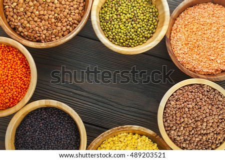 Wooden bowls of various lentils on a wooden background